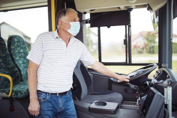 Hombre con mascarilla junto al volante de autobús
