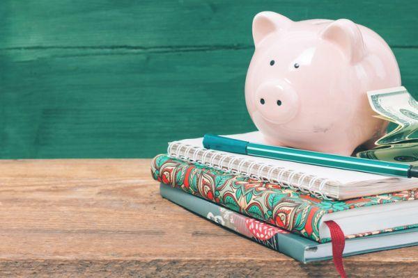 Becas usal requisitos hucha y dinero sobre cuadernos