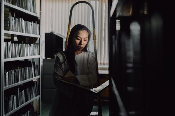 Joven leyendo entre pasillos de libros