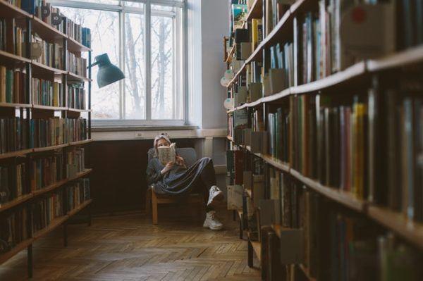 Mujer leyendo relajada en biblioteca