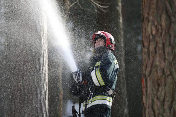 Bombero con espuma apagando fuego