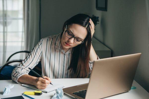 rutinas-de-estudio-en-casa-joven-estudia-camisa-de-rayas-istock